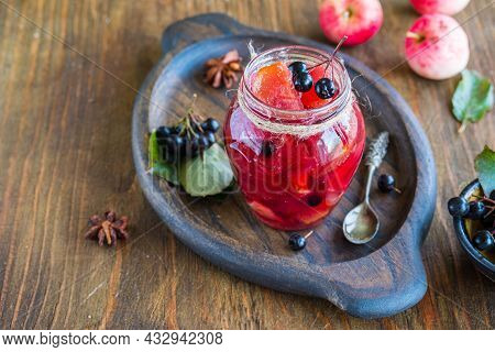 Apple Jam With Apple Pieces And Chokeberry In A Jar On A Brown Wooden Background. Jam Recipes. Canni