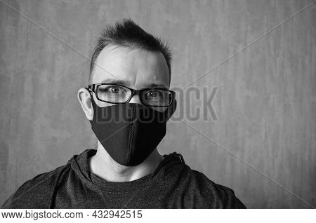 Caucasian Man With Glasses In Protective Mask On Gray Background With Copy Space. Portrait Of Smilin
