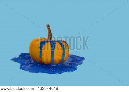 Creative Autumn Idea. Fresh Pumpkin With Shiny Dripping And Melting Paint On F Background