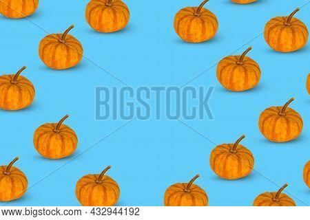 Modern Autumn Pattern Of Orange Pumpkins On A Blue Background.