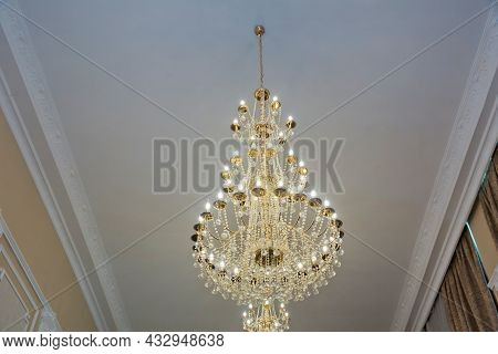 Reflecting Sun Day On The Large And Bright Chandelier. Yellow Rays Of Sun. Chandeliers, Beautiful Li