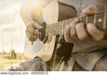 Guitarist playing acoustic guitar outside in a field in the summer sunshine