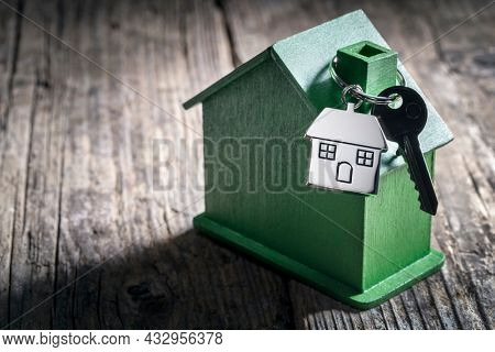 House key on a house shaped keychain with green wooden home concept for real estate, moving home or environmentally friendly property