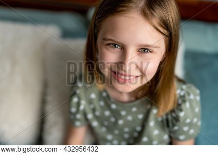 Closeup portrait og cute preteen kid girl looking at the camera and smiling. Little schoolgirl model with pretty face in the bedroom