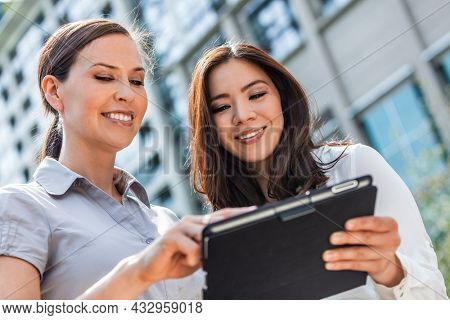Business team of two successful women, mixed race group of businesswomen, Asian and Caucasian using a tablet computer in a modern city