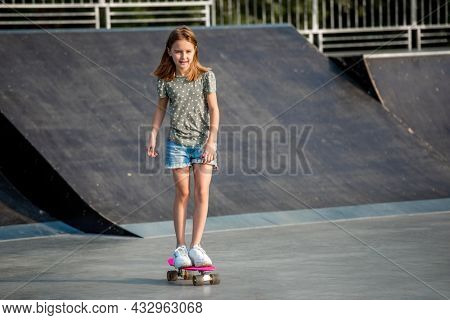 Preteen girl riding on skateboard at park ramp in summertime. Beautiful female child skater with board outdoors practicing