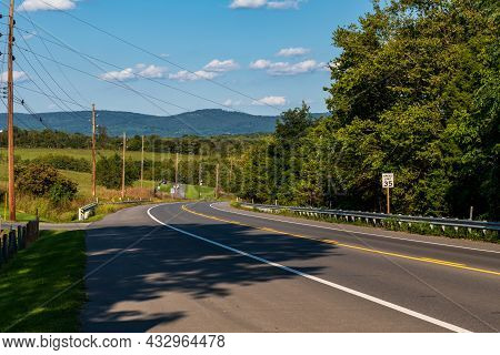 A Two Lane Road Going Downhill In Sharpsburg, Maryland, Usa On Sunny Summer Day