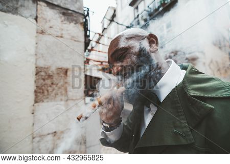 A Side View Of An Elegant Mature Bearded Black Guy In A Dark-green Fashionable Outfit Smoking A Ciga