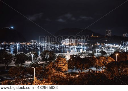Long-exposure Night Urban Landscape With A Bay With Boats And Vessels In The Background And The Grou