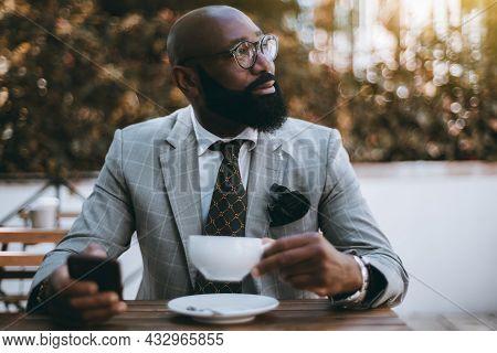 A Portrait Of A Mature Black Senior Entrepreneur Sitting In A Street Cafe With A Cup Of Delicious Te