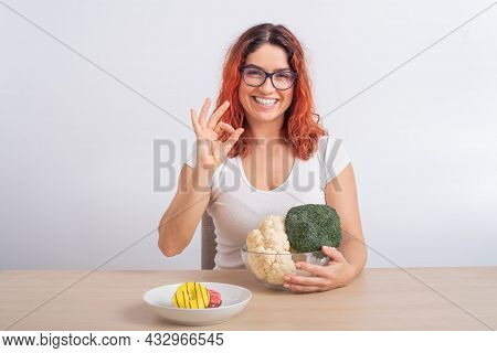 Caucasian Woman Prefers Healthy Food. Redhead Girl Chooses Between Broccoli And Donuts On White Back