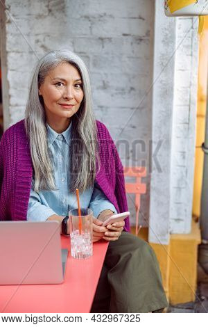 Positive Mature Asian Lady With Straight Hair Holds Mobile Phone At Table With Notebook