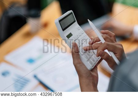 Woman Entrepreneur Using A Calculator With A Pen In Her Hand, Calculating Financial Expense With Wor