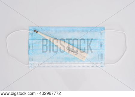 Close-up Of Surgical Medical Mask And Thermometer On White Background