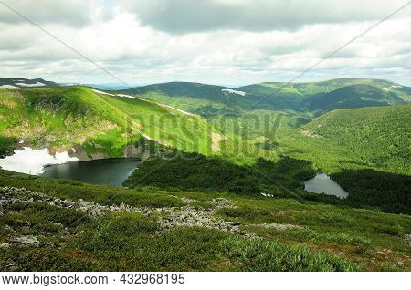 A Top View Of The Peaks Of The Mountain Range And The Picturesque Lakes Lying Below Under A Cloudy C