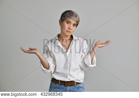 Image Of Confused Puzzled Upset Middle Aged Asian Woman Standing Isolated Over White Background. Loo