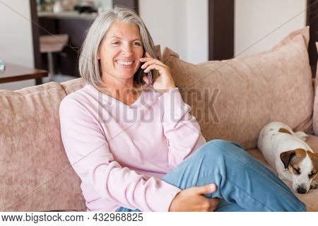 Pleased middle-aged white woman talking on mobile phone on couch in living room. Happy gray-haired mature female sitting on sofa at home