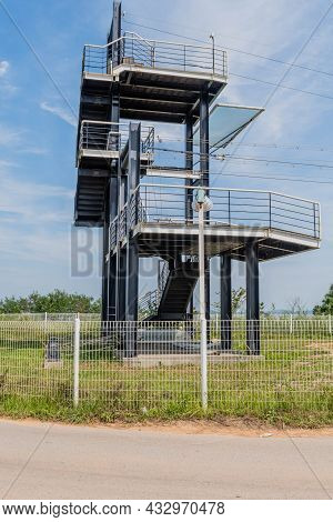 Multilevel Observation Tower Under Blue Cloudy Sky In Countryside Park.