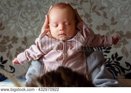 Mother Holding Her Caucasian Newborn Baby Girl In Hands. Top View. Baby Sleeping In Mums Hands. Conn