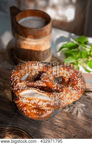 Fresh Pretzel On A Rustic Wooden Table With A Wooden Beer Mug. Rustic Style.
