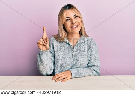 Young caucasian woman wearing casual clothes sitting on the table smiling with an idea or question pointing finger up with happy face, number one