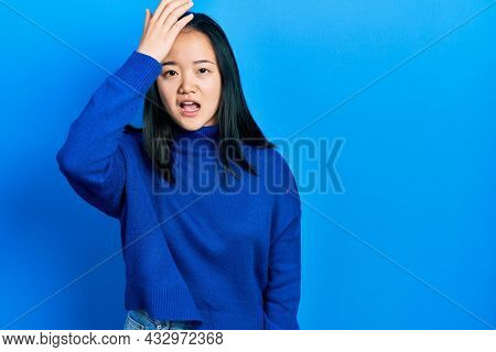 Young chinese girl wearing casual clothes surprised with hand on head for mistake, remember error. forgot, bad memory concept.