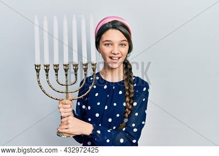 Young brunette girl holding menorah hanukkah jewish candle celebrating crazy and amazed for success with open eyes screaming excited.