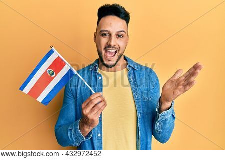 Young arab man holding costa rica flag celebrating achievement with happy smile and winner expression with raised hand
