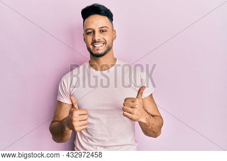 Young arab man wearing casual clothes success sign doing positive gesture with hand, thumbs up smiling and happy. cheerful expression and winner gesture.