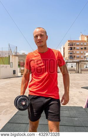 Vertical Shot Of Handsome Muscular Man Lifts Dumbbell Outdoor, Gets Ready For Weight Lifting Trainin
