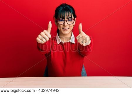 Young brunette woman with bangs wearing glasses sitting on the table approving doing positive gesture with hand, thumbs up smiling and happy for success. winner gesture.