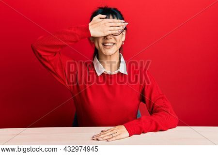 Young brunette woman with bangs wearing glasses sitting on the table smiling and laughing with hand on face covering eyes for surprise. blind concept.