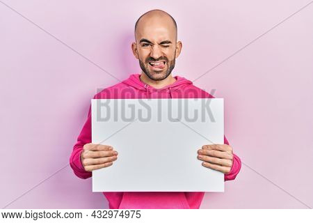 Young bald man holding blank empty banner sticking tongue out happy with funny expression.