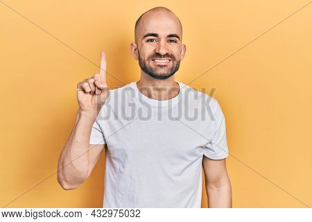 Young bald man wearing casual white t shirt showing and pointing up with finger number one while smiling confident and happy.
