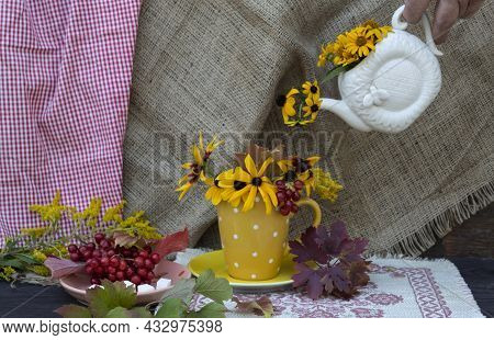 A Hand Holds A Teapot, From Which Autumn Flowers Are Pouring Into A Yellow Cup. Nearby There Is A Sa