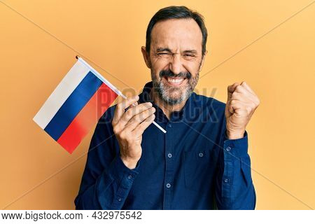 Middle age hispanic man holding russia flag screaming proud, celebrating victory and success very excited with raised arm