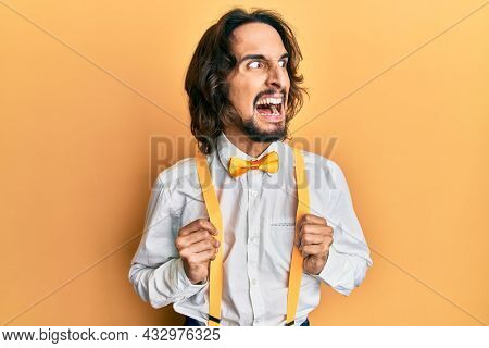 Young hispanic man wearing hipster elegant look angry and mad screaming frustrated and furious, shouting with anger. rage and aggressive concept.