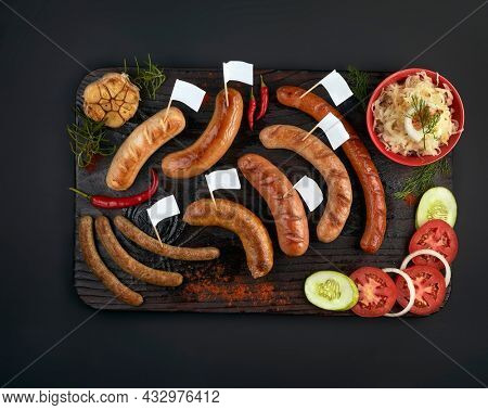 Set of 7 kind of grilled sausages with flags for copy space text, sauerkraut, vegetables, mustard, chili on black board over black background