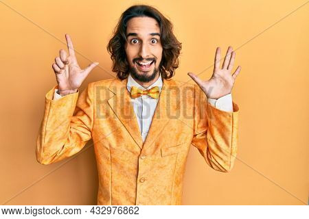 Young hispanic man wearing hipster elegant look showing and pointing up with fingers number seven while smiling confident and happy.