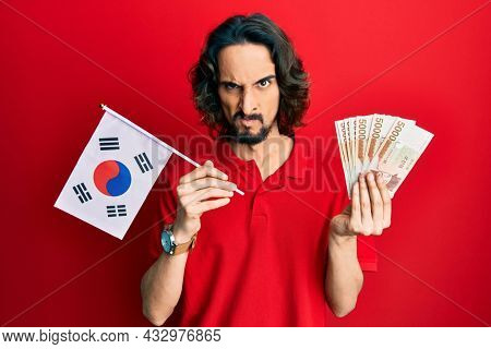 Young hispanic man holding south korea flag and won banknotes skeptic and nervous, frowning upset because of problem. negative person.