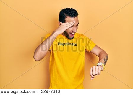 Hispanic man with beard wearing t shirt with happiness word message looking at the watch time worried, afraid of getting late
