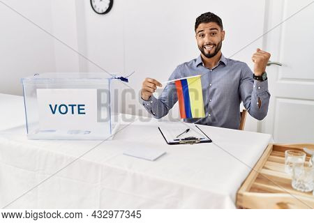 Young handsome man with beard at political campaign election holding colombia flag screaming proud, celebrating victory and success very excited with raised arms