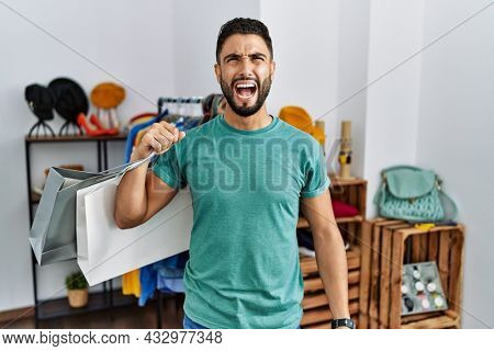 Young handsome man with beard holding shopping bags at retail shop angry and mad screaming frustrated and furious, shouting with anger. rage and aggressive concept.