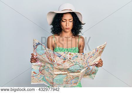 Young latin girl wearing summer hat holding city map depressed and worry for distress, crying angry and afraid. sad expression.