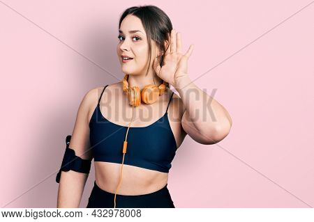 Young hispanic girl wearing gym clothes and using headphones smiling with hand over ear listening and hearing to rumor or gossip. deafness concept.