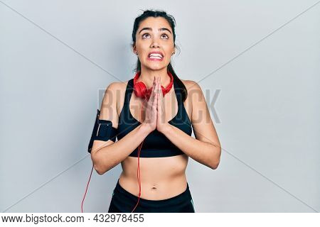 Young hispanic girl wearing gym clothes and using headphones begging and praying with hands together with hope expression on face very emotional and worried. begging.