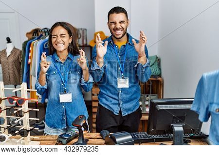 Young interracial people working at retail boutique gesturing finger crossed smiling with hope and eyes closed. luck and superstitious concept.