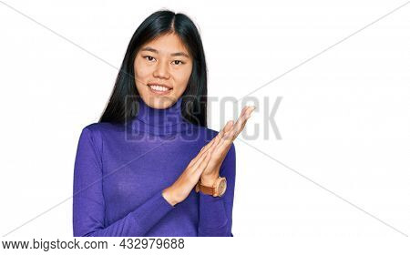 Beautiful young asian woman wearing casual clothes clapping and applauding happy and joyful, smiling proud hands together