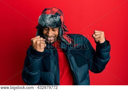 Young african american man with beard wearing winter hat and coat excited for success with arms raised and eyes closed celebrating victory smiling. winner concept.