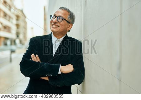 Middle age southeast asian man smiling confident with crossed arms leaning on the wall